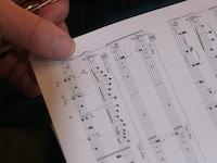 Noter i hendene til korsanger briller